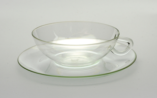 (a) Clear blown glass cup wide with applied handle in solid glass in C-shape with flat upper section. (b) Circular saucer with curved edge and depression for cup.