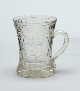"Beaker shape, tapered at middle; scalloped base; loop handle cut with notches; sides cut with band of tall diamonds with central printies, the central panel engraved ""Erinerung."""