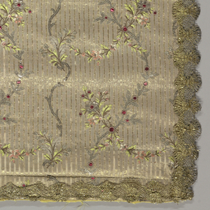Fabric with floral sprays in pinks, greens and metallic heightened by metallic applique. Panel finished with gold colored metallic bobbin lace.