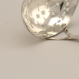 Pointed oval bowl pierced with three stars and radiating trefoils within an alternating hourglass and egg border. The bowl with scalloped edge. The bifurcated stem issuing rounded, pointed terminal engraved with flower head within dot engraved border.