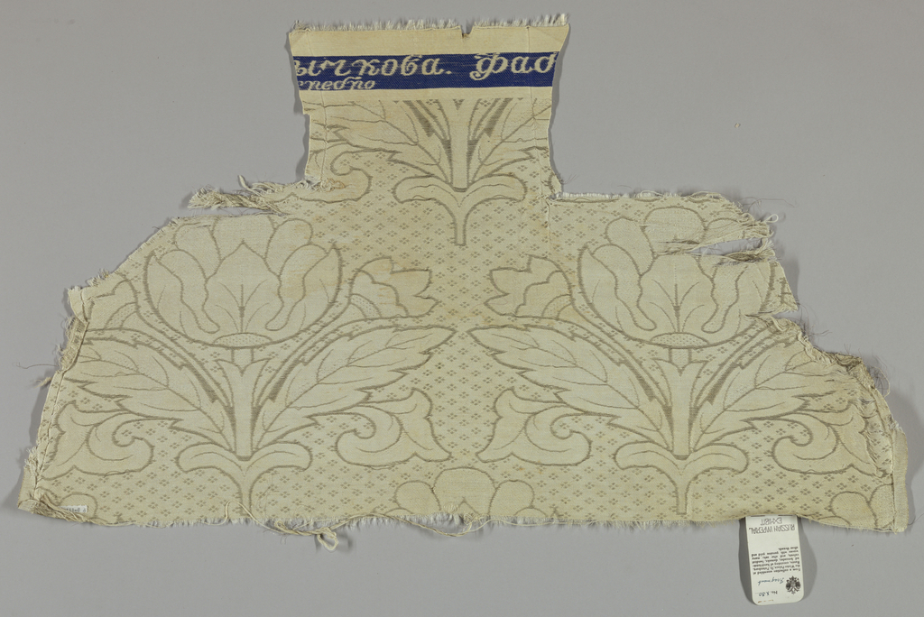 Diagonal repeat of large symmetrical tulip-like flowers with smaller tulip and broad-toothed leaves on either side of stem. Diamond rosette diaper filling interstices. In tarnished white metal threads in plain and fancy twill and coarse white satin ground. Wide plain cloth selvages. Plain satin area on top with fragmentary woven inscription in white on blue band.