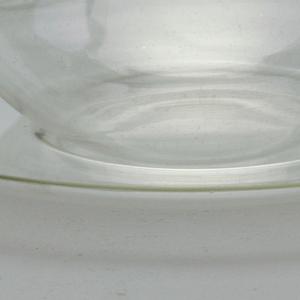 Shallow hemispherical cup, loop handle.  Concave circular saucer.