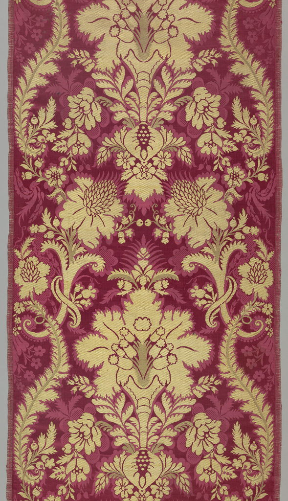 Red silk satin damask brocaded in gold in a vertically symmetrical design of flowering plants.
