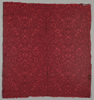 Orange silk warp and dark red wool weft. Scrolling symmetrical floral pattern rising vertically.