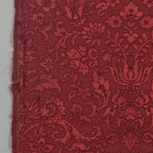 Orange silk warp and dark red wool weft. Scrolling symmetrical floral pattern rising vertically.