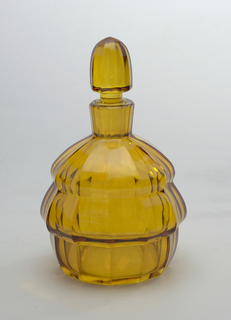 Amber-colored glass bottle with stepped bell-shaped body and vertical striations; bell-shaped stopper.
