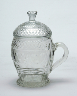 Ovoid body; flared foot, fluted, with radial cutting on bottom; loop handl cut with notches; domed lid with tall faceted finial; body cut with centralband of swags, printies, & a tiny diamond background, a band of diamonds above and prismatic rings and flat fluting below; glass greenish, light.