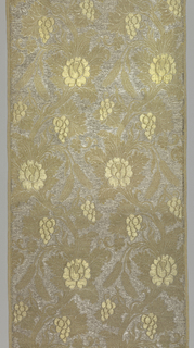Solid gold and silver brocade. Design of serpentine branches with blossoms, grapes and wheat. Grapes and blossoms are in high relief.