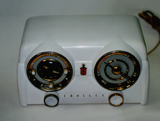 White rectangular housing with two large circular speakers on front, each with a white and gold circular plastic dial below; left speaker with yellow metal clock face and three small white dials, right speaker with yellow metal tuning dial; small circular knob under each speaker. Red sheild-shaped logo between the two speakers.