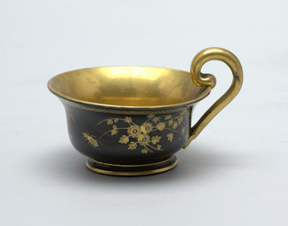 Gold and black decoration,gold cup interior and handle; exterior black with gold decoration (floral and animal). Saucer black with gold geometric border and gold floral and animal decoration.