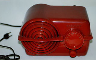 Red rectangular radio with left side rounded. Speaker on left is concentric circles with horizontal line crossing entire face and sides. On right, plastic control dials, one large over one small.