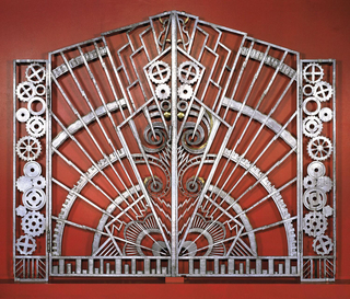 Paired with gate -1.  This gate composed of two sections: a smaller tall rectangular section (positioned at outer left side) and a larger trapezoidal section (that joins with paired gate), the two sections hinged together with two large hinges.  Inside smaller section are 14 cogwheels stacked up irregularly; along the bottom edge a border made up of straight and diagonal lines.  Larger section has radiating pattern of bolts of electricity or lightening and sky-scraper-like shapes that emanate from lower right inside corner.  Four concentric rings of cogwheel-like form also emanating from lower right inside corner.  Bolts of electricity, cogwheels, spirals, and other shapes interspersed along inside edge.  Bottom edge has a border of stacked coins.