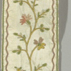 White taffeta, in long vertical strip for border. Green line and inner brown serpentine line on outer edges. Central serpentine small-scale flowering vine embroidered in chain stitch with green, yellow, brown, pink silks. Both A/ and B/ have a selvage present.