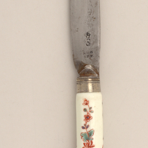 Saber-shaped blade with drop bolster. Plain silver ferrule with horizontal bands. Pistol-shaped white porcelain handle. Octagonal in section. Floral design in green, blue and brown-red. Silver button at the top of the handle.