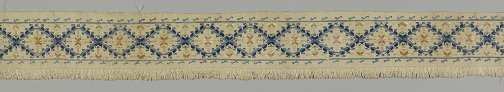 Band of white linen with embroidery in a design of lozenges with flowers in center. Narrow border of conventional ornament on either side. White linen fringe on one edge.