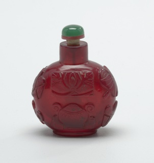 Monotone cameo-glass, ruby red; carved with eight precious emblems of good fortune; wheel of law, conch shell, umbrella canopy, lotus flower, pair of fish, endless knot. Flattened globose shape. Stopper of green glass simulating jade and set on pale red glass. Ivory spoon.