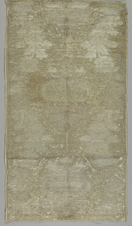 Single panel of silver and white metal cloth. Design of broad serpentine bands of flowers and foliage alternating with vertical repeat of large symmetrical floral sprays.