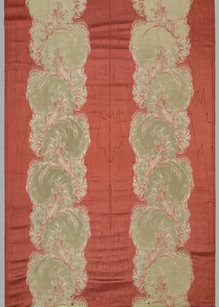 Orange-red ribbed silk moiré, with design of yellow plumes arranged in two vertical columns.