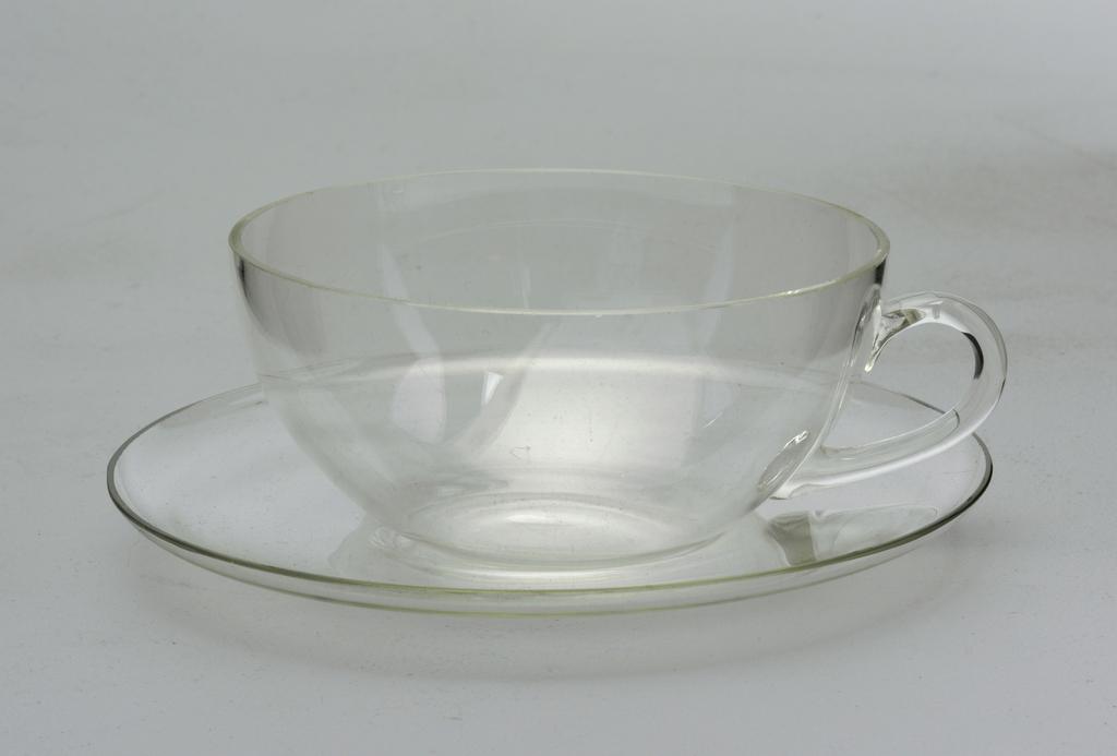 Shallow hemispherical cup with loop handle.  Concave circular saucer.
