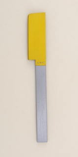 Flat rectangular handle of grey aluminum; brushed surface. Rectangular aluminum blade, anodized yellow, with rounded outer point and bevelled cutting edge. Blade affixed to handle side with three silver rivets.