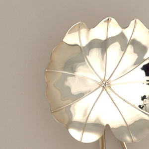 Silver server composed of nasturtium leaves with thin vine for handle.