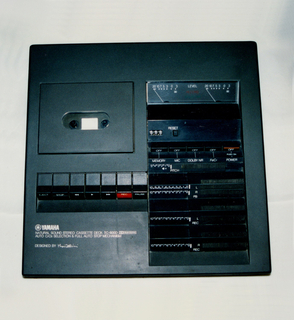 Forward tilting square cassette deck, housing of grey ABS plastic. Cassette compartment with flip-up door on the upper left hand corner, row of control switches below; vertical rectangular panel of read-outs and additional controls on the right side.