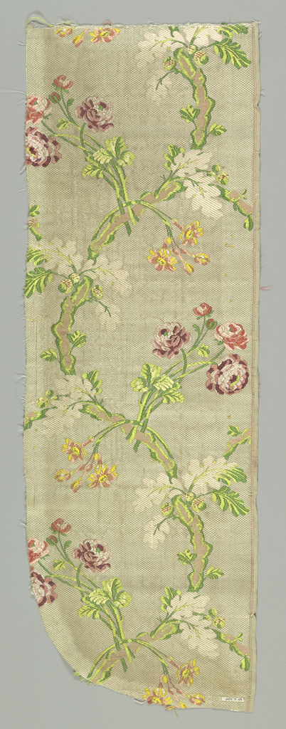 White ground with large serpentine branch from which spring sprays of realistically drawn flowers, acorns and foliage, brocaded in polychrome silks.