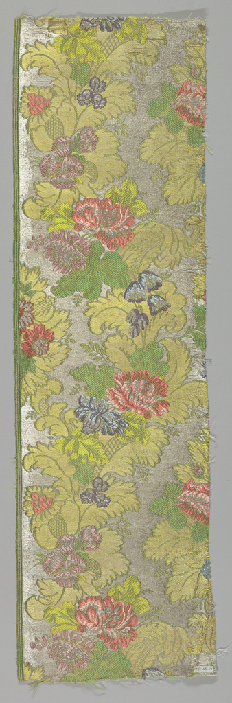 Flowers and acanthus leaves in gold on silver background. Flowers shaded red, blue, violet and green. Fragment has trimming of silk stripes.