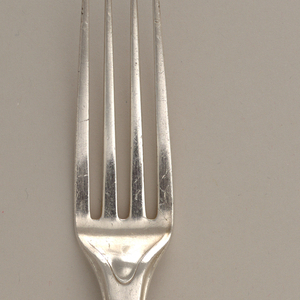 Four tines; long handle tapers then swells at end, with two concave lobes.  Back side has engraved oval near head and long lines extending down sides.  JO monogram in square near end of handle, backside.