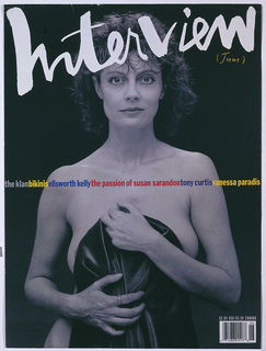 "Magazine cover of a black and white nude photograph of Susan Sarandon standing while holding a black cloth in front of her.  At the top ""Interview"" written in white lettering."