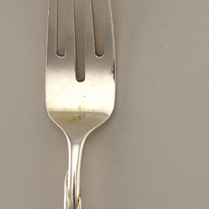 Handle of gentle s-curve shape, modeled to suggest leaves from which rises stem with head of fork; four tines.  Back side modeled with parting leaves as base of fork head.