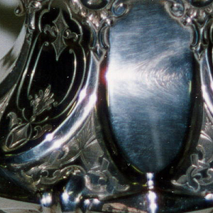 Ogival footed silver sugar bowl; pointed handles; engraved with plant forms in cartouche-like areas. Gilt interior.
