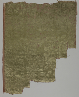 Brick red cloth ground completely covered by two heights of gray-green silk pile: diagonal repeat giving all-over effect of debased design of scrolling arabesques outlined in tarnished metal; coarse chain-stitch done by machine. One wide selvage with double warps and wefts in brick red with narrow vertical stripes with beige warps from same house.