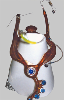 Flexible, transluscent brown resin collar-like form with upright projections on left and right sides, one with small yellow vertical bar at eye level representing a retinal scanning computer display, the other an ear piece; front projection with small circular microphone; pendant-like lower section with five blue discs representing computer trackball and four touch keys to activate computer software.