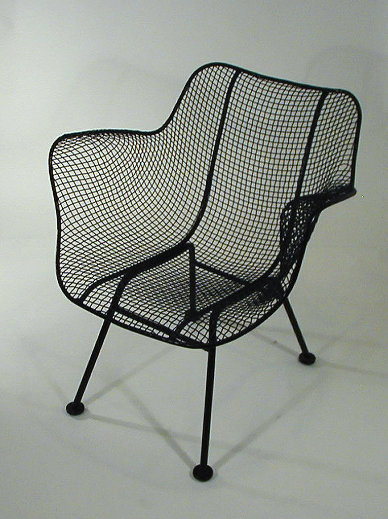 Form composed of contoured black wire mesh back/arms/seat unit on four thin, black cylindrical legs; circular pad feet.