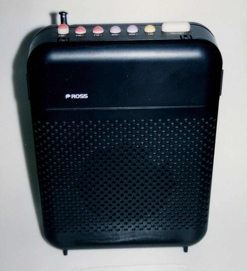 Upright black rectangular radio with rounded corners; lower three-quaters of front perforated with circular holes for speaker. Top with seven white, orange, pink, and yellow control buttons and retractable metal antenna on left; black front panel flips up to reveal additional colored control buttons, dials and switches.