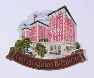 Luggage label depicting a brick building constructed in three towering sections. American flags fly atop the hotel, trees grow in front. Text, metallic gold, in a scroll swag: Los Angeles Biltmore.
