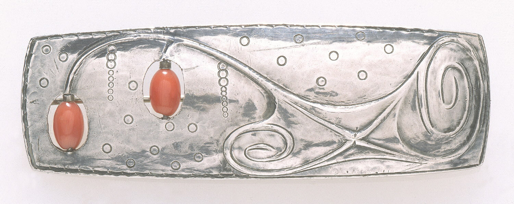 Rectangular, horizontal form with out-curved edges; surface chased with dots and abstract decoration reminiscent of curling plant stems with two coral beads depending in holes pierced in form; clasp on back side.