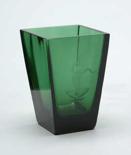 Green glass vase is square, with sides tapered in toward flat base. Lip is flat and horizontal. Acid-engraved front is semi-nude female figure seated cross-legged and with arms raised.