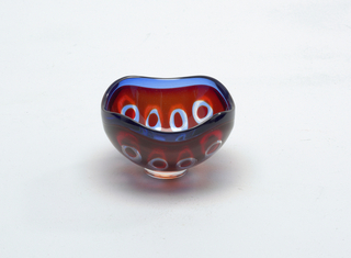 Red glass with blue accent.  Clear glass circular decoration on body