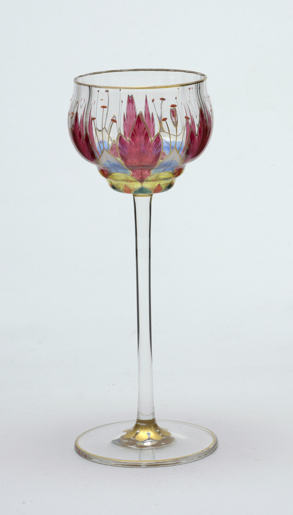 A) Decanter with pear-shaped body of clear glass with stemmed foot and tall, slender, 12-ribbed neck.  stylized floriform decoration around body in orange-red, blues, orange, yellow, green and white with gilded outlines; gilding on lip and foot.   B-G) wine glasses with rounded bowls, stepped at bottom and with slightly flaring lip on tall slender straight stems.  Decorative pattern identical with that of decanter except that purple-red is used instead of orange-red.