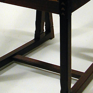 Chair with slightly straight back and seat; both upholstered in beige fabric; straight legs with stretchers at ground level. Decorated at legs and back frame: colored square inlay.