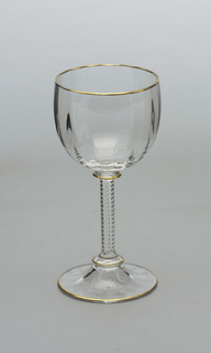 Mouth-blown crystal wine glass, with a twisted stem and a structured cup with gold rims.