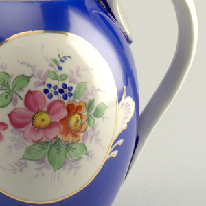Round teapot, allover blue and gilt-bordered medallion depicting flowers; long curved spout, white knob and C-curved white handle; gilt rim around top opening of teapot.