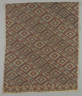 Polychrome silks, predominantly red and green, solidly worked in cross stitch on cotton canvas in diagonal rows of lozenges separated by narrower diagonal bands; all forms built up of minute floral motifs. Vertical border at one end.