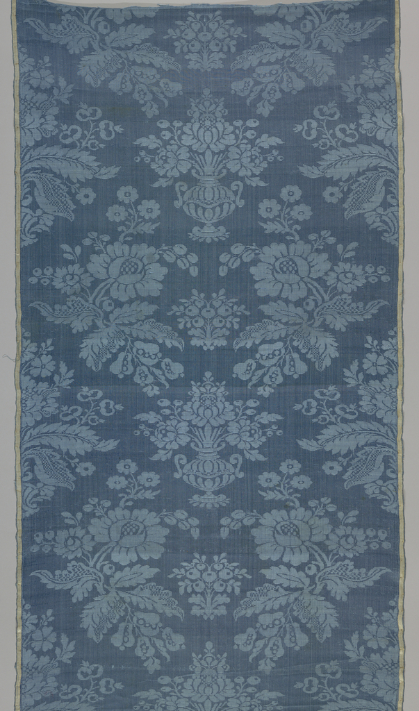 Mazarin blue damask with design of lateral rows of curving peony branches with diapered foliage alternating with floral vases. Faded pink and white satin selvages.