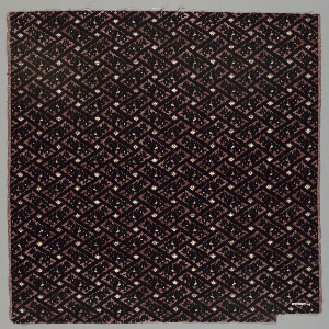 Opposing rectangles of black warp pile form a loose lattice framework with flower blossoms in each rectangle. A diamond-shaped blossom fills the open spaces of the lattice. Foundation is a dark reddish-orange.