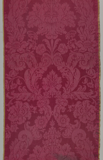 Short length of red damask in a symmetrical arrangement of flowers and leafy scrolls.