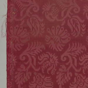 Red damask patterned by two offset rows of flowering plants; a different plant in each row.