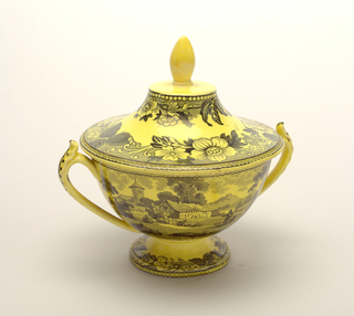 Pedestal bowl with two strap handles; shallow, bell-shaped lid with ovoid finial; circular under-plate; all having yellow ground with black transfer decoration, bowl showing house in landscape; floral decoration on foot and lid.